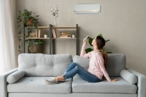 woman-turning-on-ductless-air-handler-with-remote